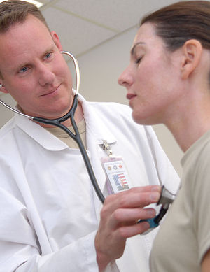 A physician performs a routine checkup on a pa...
