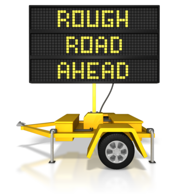 """highway construction sign saying """"rough road ahead"""""""